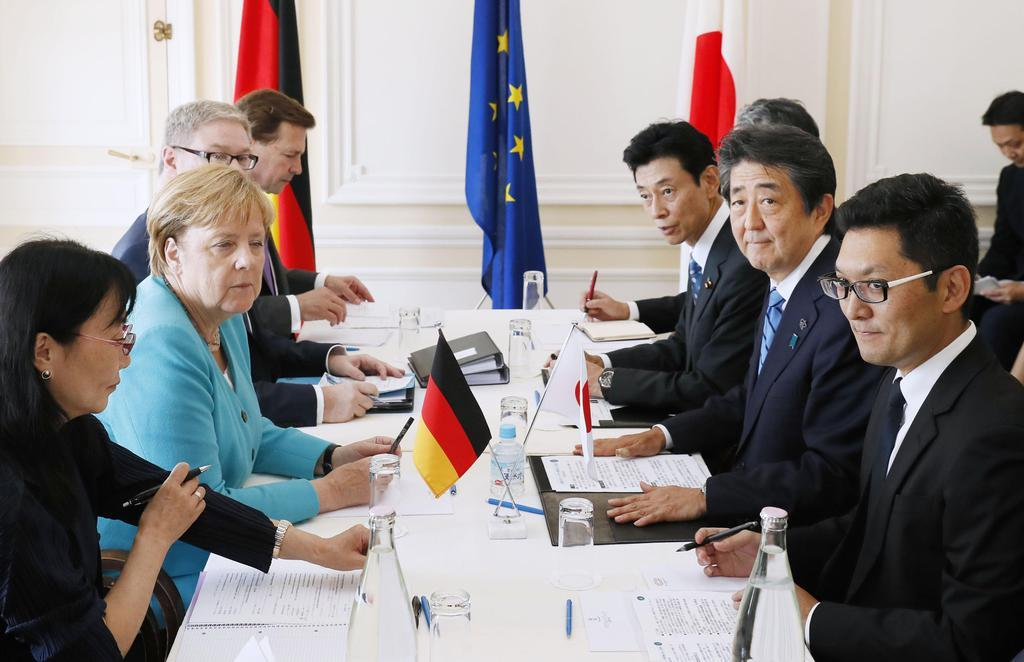 ドイツのメルケル首相(左から2人目)と会談する安倍首相=24日、フランス南西部のビアリッツ(共同)