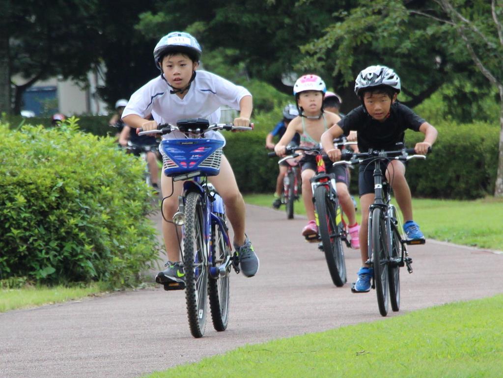 キッズトライアスロン大会のバイク競技で懸命に自転車をこぐ児童ら=25日、那須塩原市高柳のにしなすの運動公園