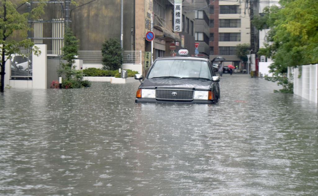 大雨の影響で道路が冠水し、立ち往生したタクシー=28日午前8時、佐賀市