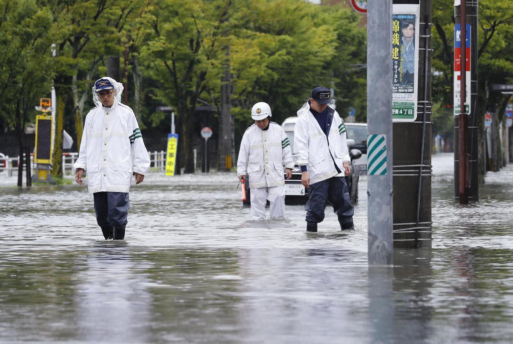 大雨で冠水した道路を見回る警察官=28日午前11時15分、佐賀市