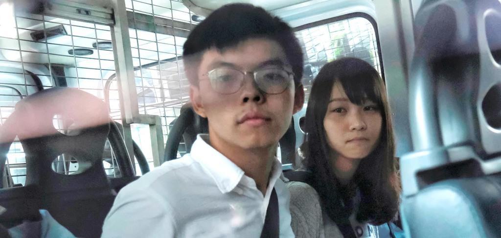 逮捕後、警察車両で裁判所に到着した黄之鋒氏(左)と周庭氏=30日、香港(ロイター)