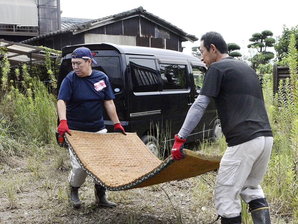 大雨による浸水被害を受けた佐賀県大町町の住宅から畳を運び出すボランティア=31日午前