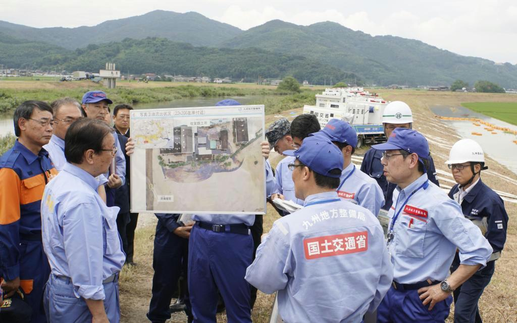 大雨による被害を受けた佐賀県大町町を視察する山本防災相(左手前)ら政府調査団