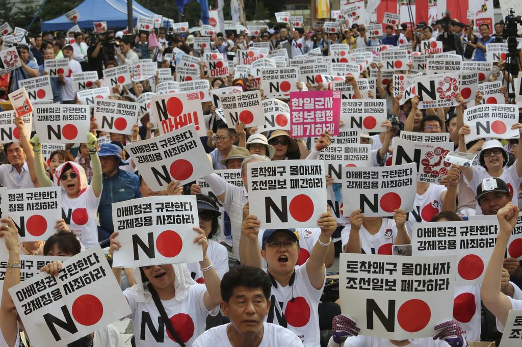 日本政府への抗議デモでは、「朝鮮日報は廃刊しろ」と書かれたプラカードを掲げる参加者も多い=8月3日、ソウルの日本大使館前(AP)