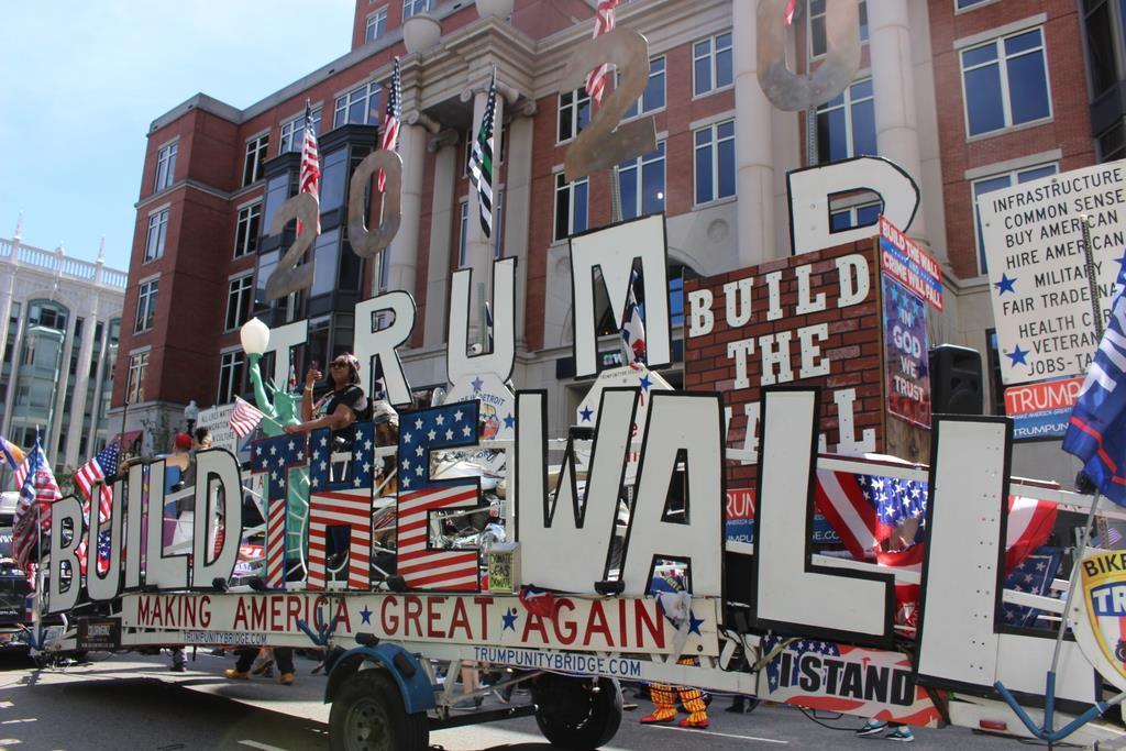 8月31日、米ボストンで行われた「ストレートパレード」の参加者を先導した車。トランプ大統領の再選を支持し、メキシコとの国境の壁建設を訴えるメッセージが掲示された(上塚真由撮影)