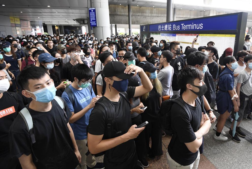香港国際空港のターミナル入り口周辺に集まったデモ隊の若者ら=1日(共同)