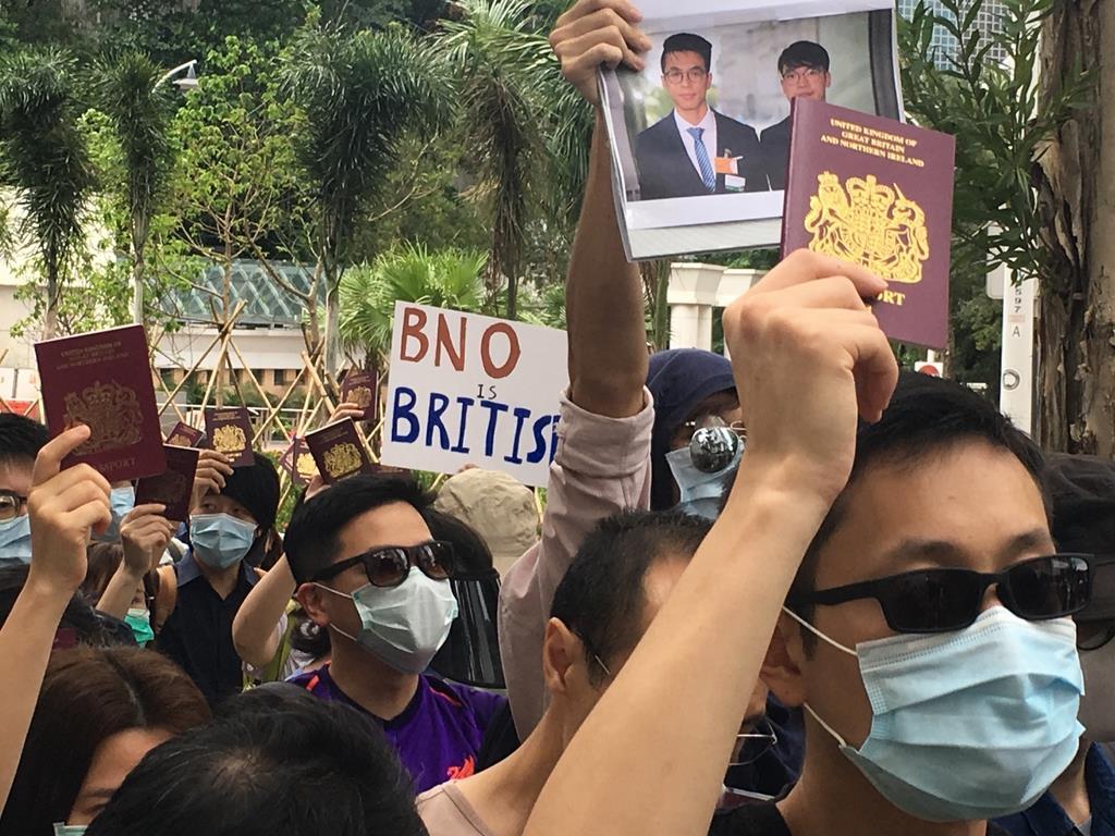 英総領事館前でBNOの旅券を掲げてデモをする市民ら=1日、香港(藤本欣也撮影)