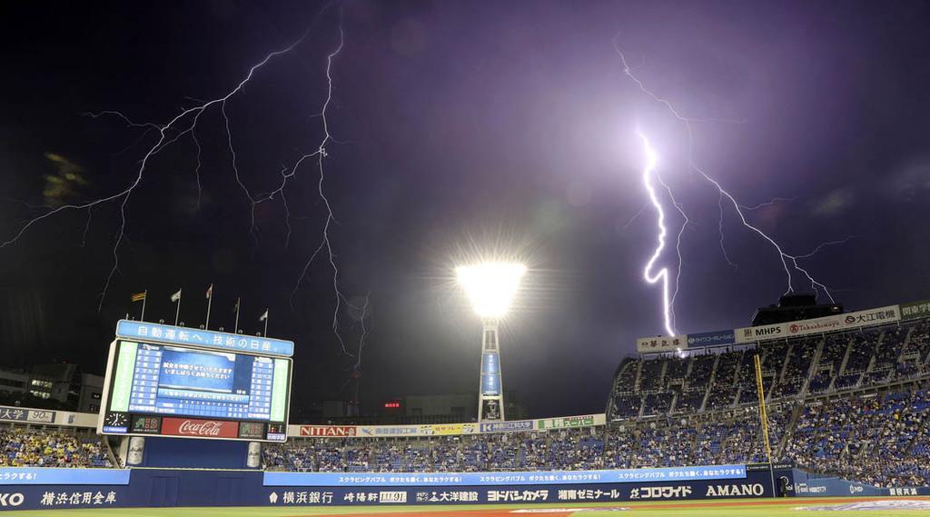 大雨に伴い、1回途中でプロ野球の試合は中断。上空に稲妻が走った=3日夜、横浜市中区の横浜スタジアム