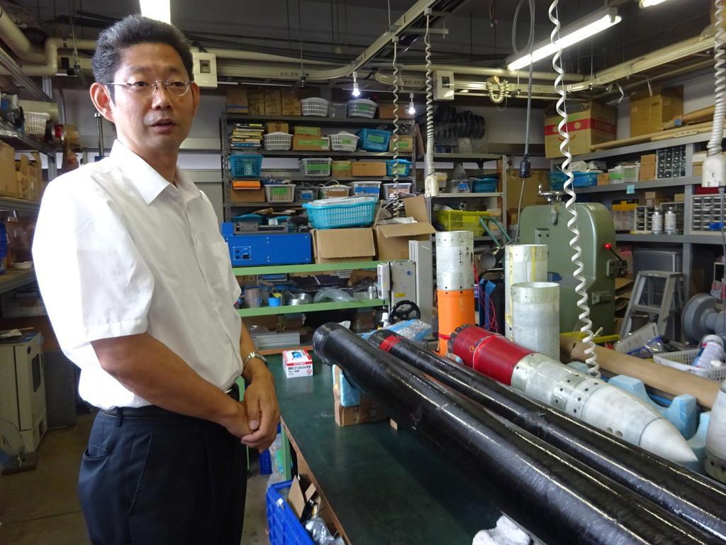 開発したロケットの先端部の横に立つ神奈川大学の高野敦准教授=横浜市神奈川区