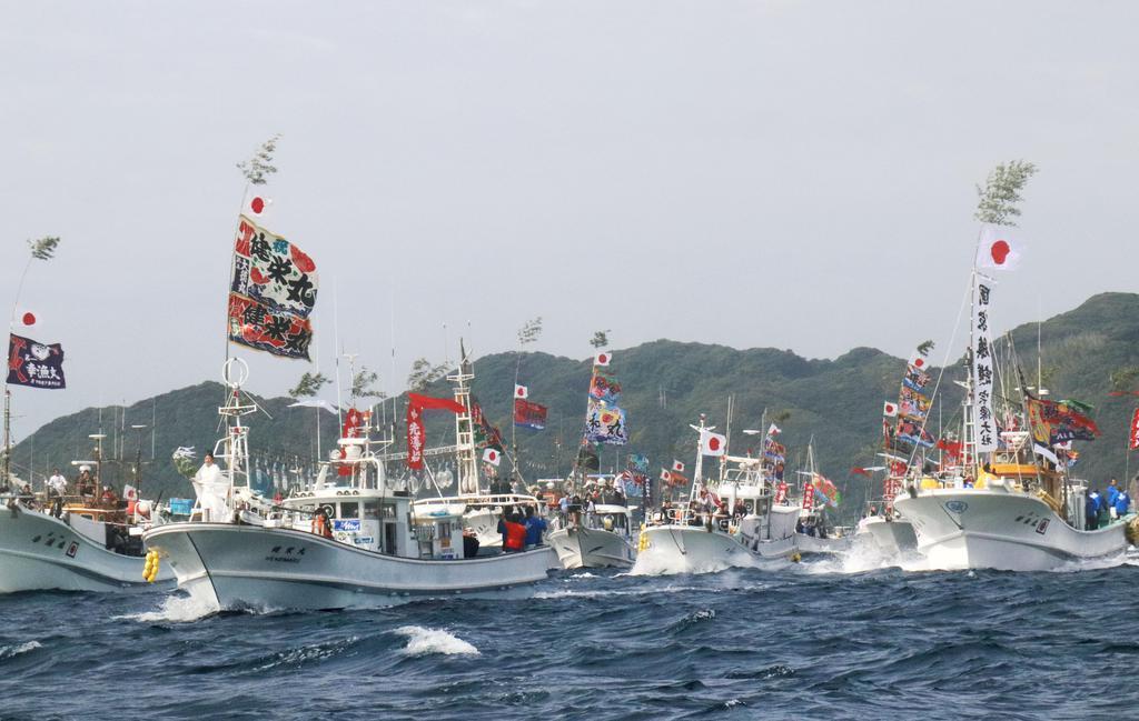 2017年に行われた宗像大社の「みあれ祭」で、大漁旗を掲げて玄界灘を疾走する漁船団=福岡県宗像市沖