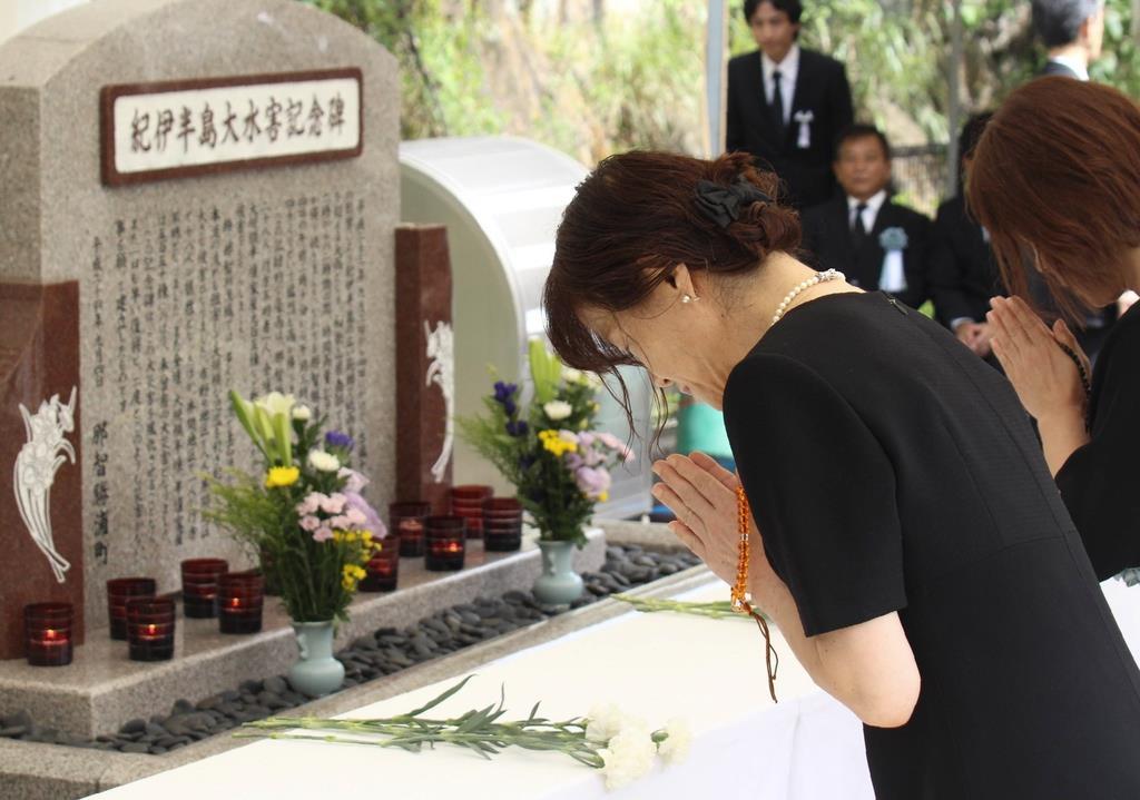 慰霊碑に手を合わせ、犠牲者の冥福を祈る参列者=和歌山県那智勝浦町