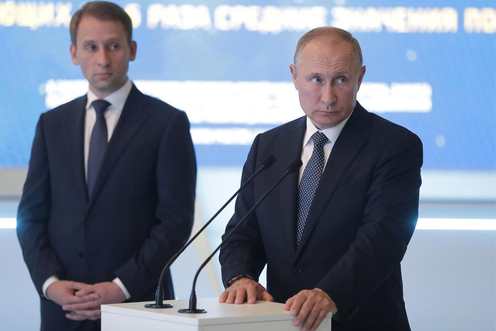 ロシア・ウラジオストクでビデオ中継に参加するプーチン大統領(右)=5日(タス=共同)