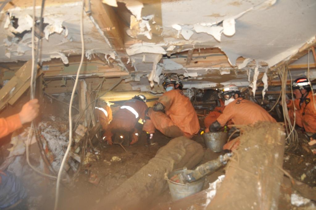 流された家屋の2階部分で救出活動にあたる消防隊員ら。右端が田中智也隊長(当時) =平成30年7月8日、広島市安芸区(大阪市消防局提供)