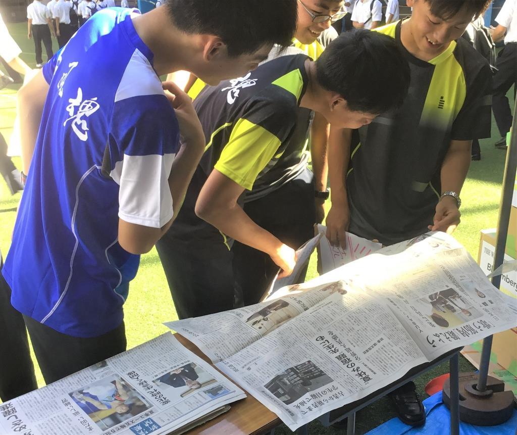 文化祭で配布された「清風新聞」に見入る清風学園中学校・高等学校の生徒たち=6日、大阪市天王寺区