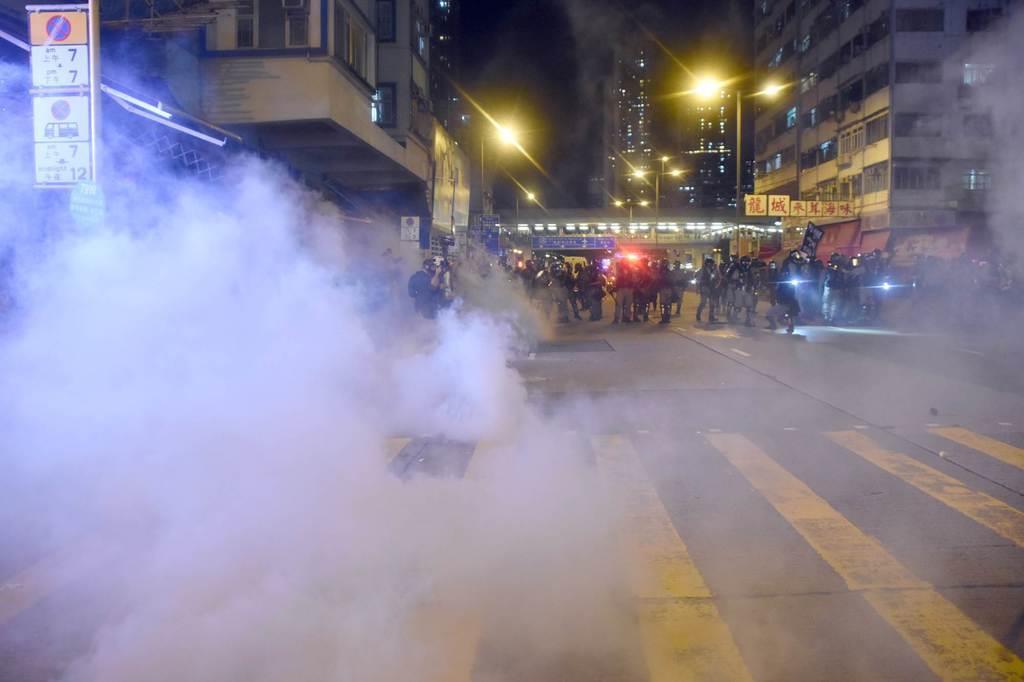6日夜、香港・モンコック(旺角)の市街地で、後退しながらデモ隊に向けて催涙弾を発射した警官隊(後方)=西見由章撮影