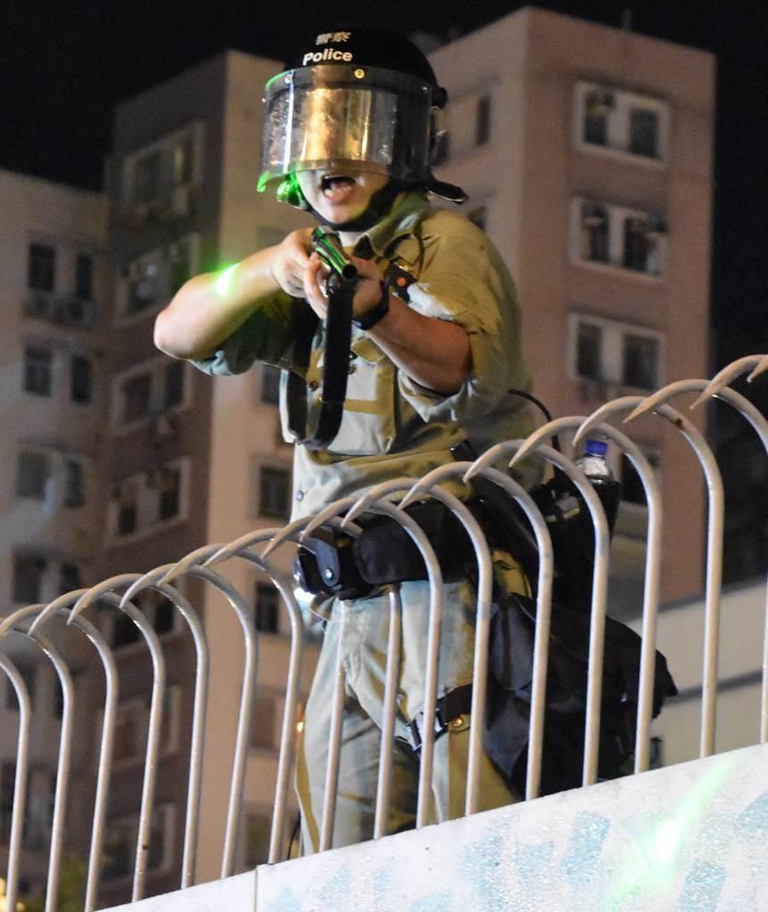 6日夜、香港・旺角警察署で、レーザーポインターの照射を浴びて怒鳴りながら銃口をデモ隊に向ける警察官(西見由章撮影)