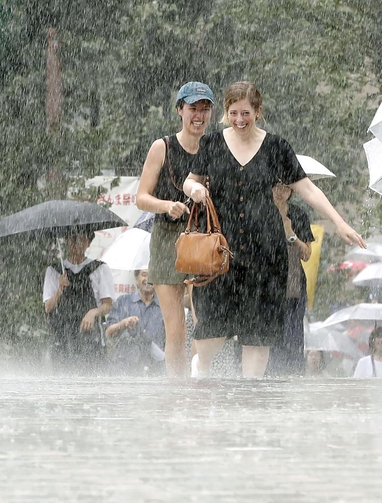 突然の土砂降りに傘を持たず、雨の中を歩く人たち=8日午前、東京都品川区