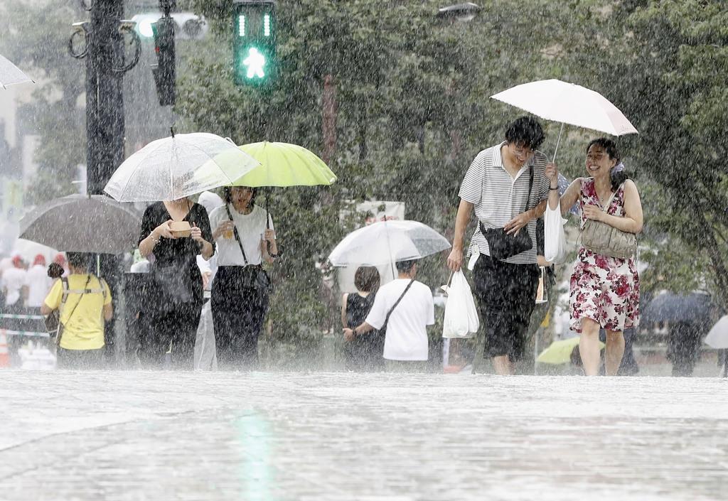土砂降りの雨の中を歩く人たち=8日午前、東京都品川区
