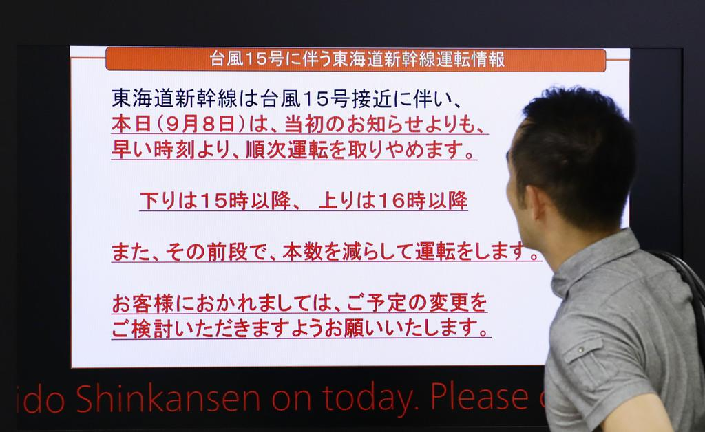 台風15号の影響で東海道新幹線の運転取りやめの予告と間引き運転のお知らせを読む男性=8日午後5時11分、JR東京駅