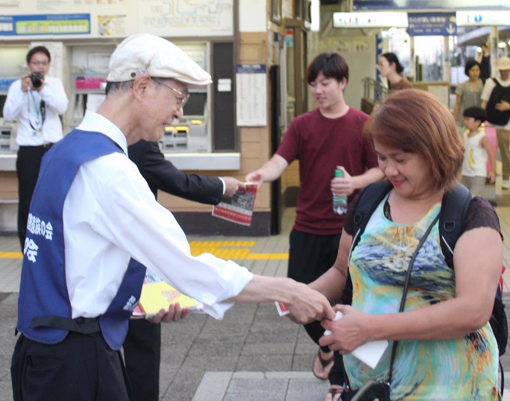 京成線柴又駅前で情報提供のビラを配る小林順子さんの父、賢二さん(左)=9日、葛飾区柴又