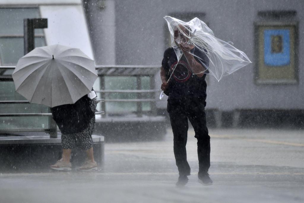 台風15号の影響で風雨が強まる中、懸命に歩く人たち=9日午前、福島県いわき市