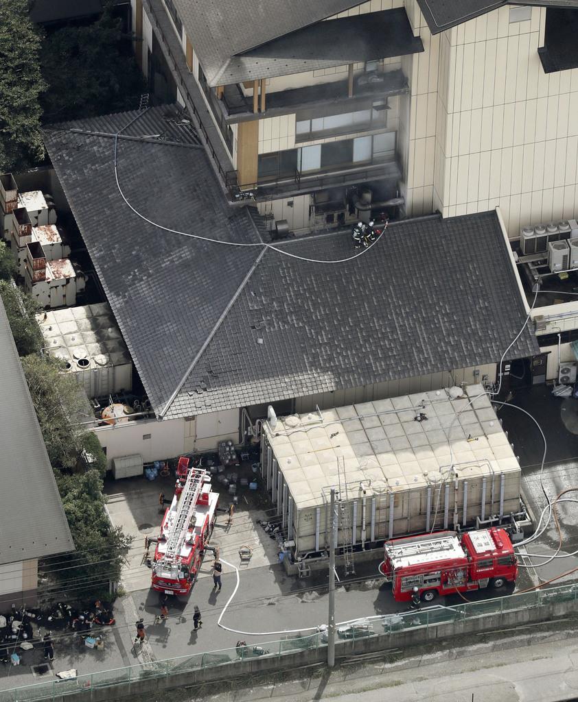 宿泊施設「ホテル三日月」で消火活動する消防隊員=9日午後、千葉県木更津市(共同通信社ヘリから)