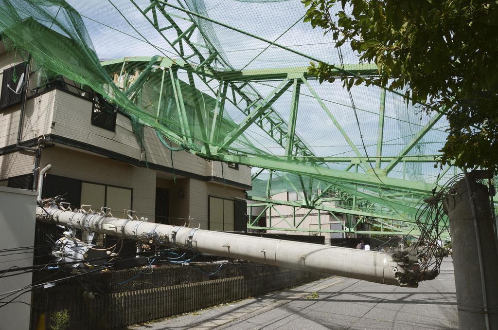 台風15号の影響で倒壊し、住宅を直撃したゴルフ練習場のポールと電柱=9日午後、千葉県市原市