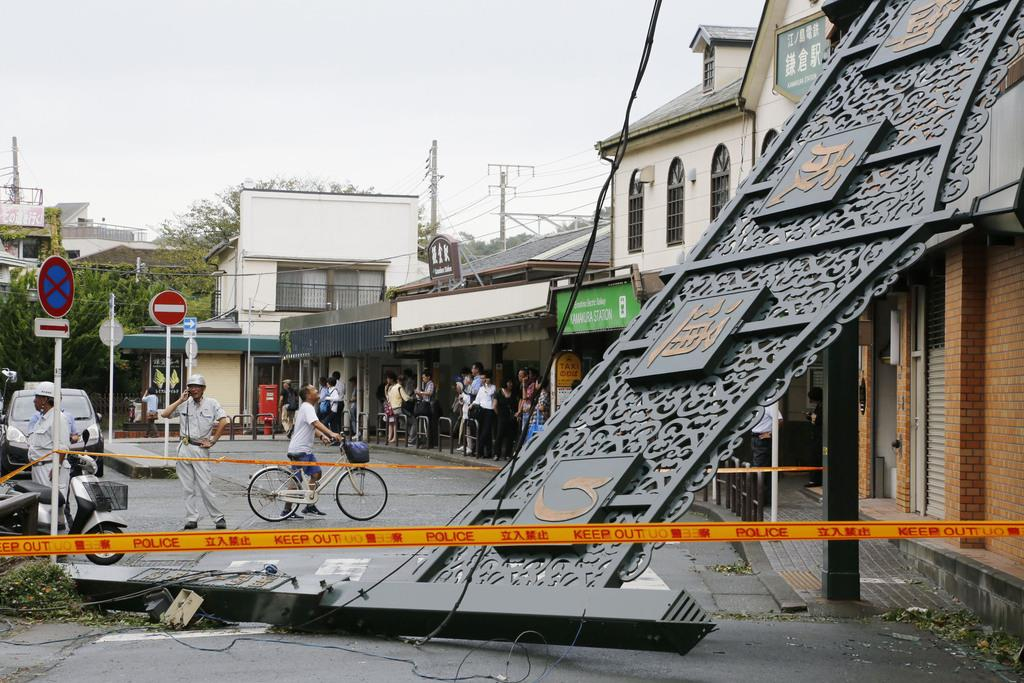 台風15号の影響で倒壊した商店街入り口の看板。後方は鎌倉駅=9日午前、神奈川県鎌倉市