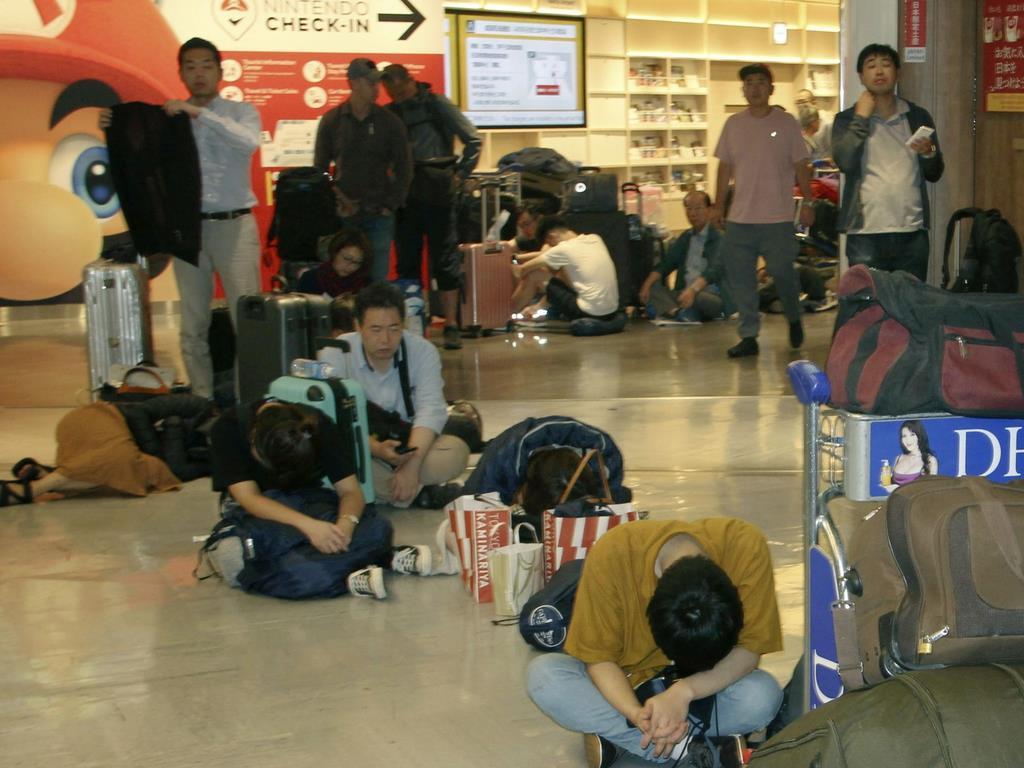 足止めされた成田空港で一夜を明かし、疲れた様子の利用客=10日午前5時1分