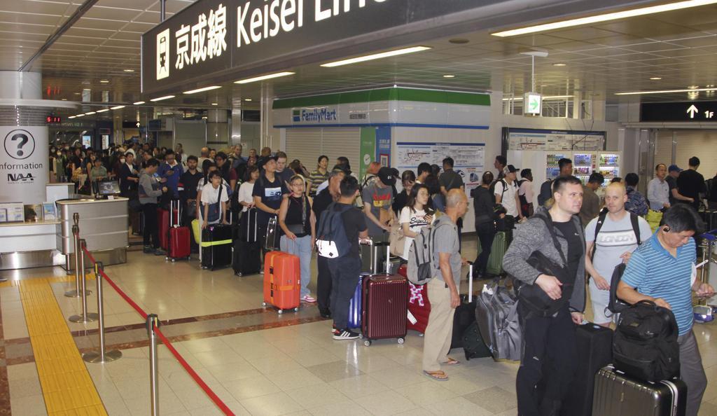 成田空港で一夜を明かし、始発の電車を待つ利用客=10日午前5時12分、成田空港