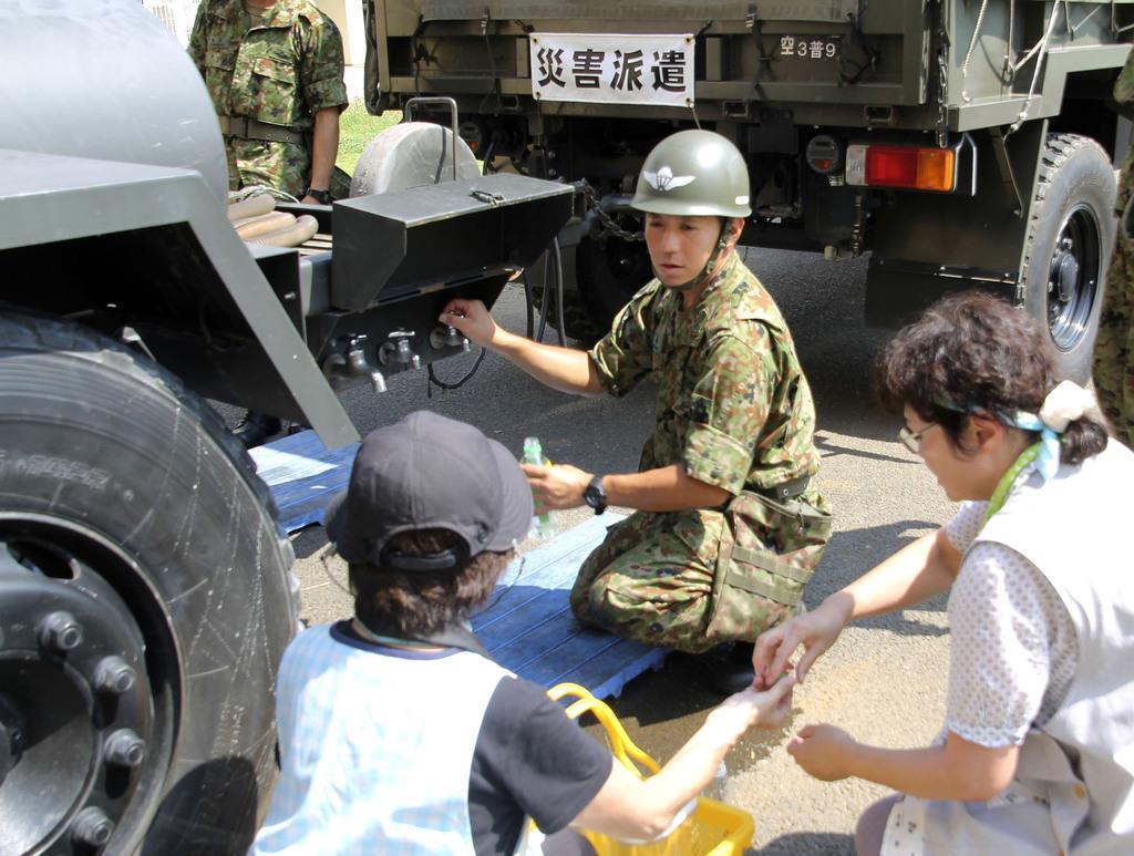 千葉県などで現在も停電が続いている。同県佐倉市内の小学校で、給水活動する自衛隊員=10日午後0時44分