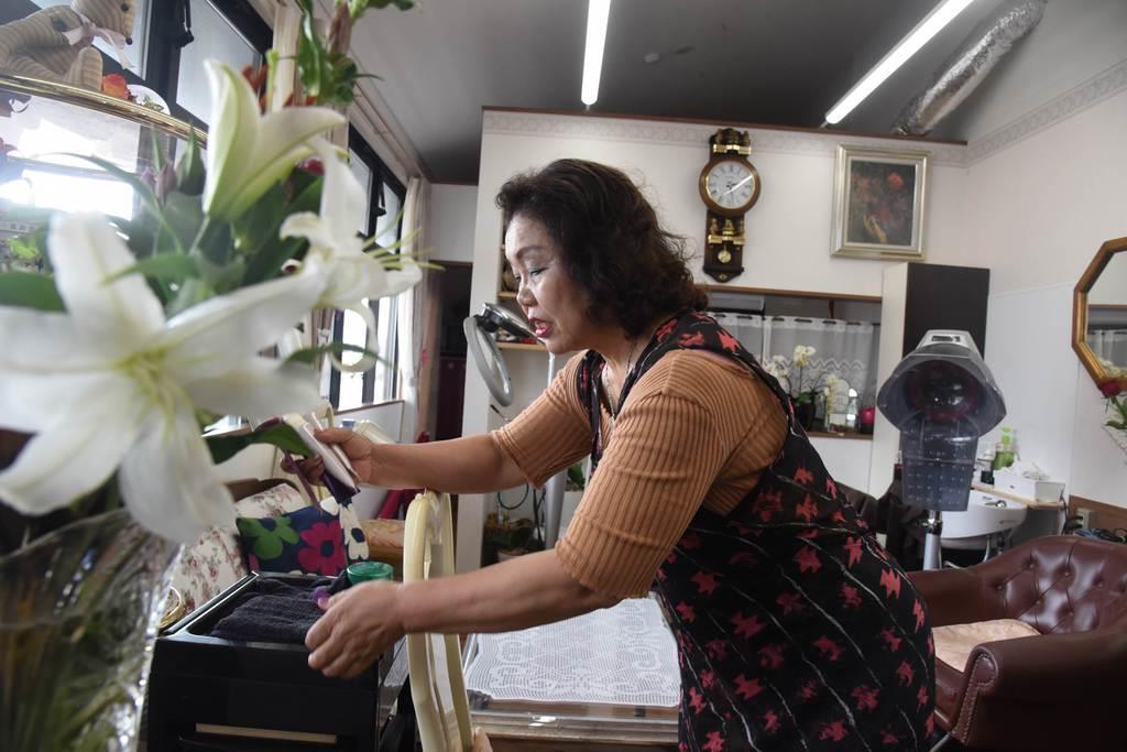 今年4月、美容室を再開した中橋さん。贈り物の花に囲まれた店内で客を待つ=宮城県名取市(千葉元撮影)