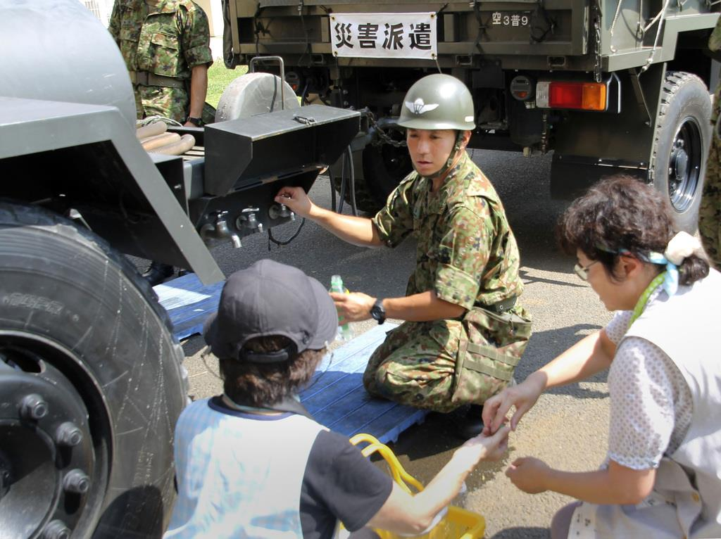 千葉県佐倉市内の小学校で、給水活動する自衛隊員=10日午後0時44分