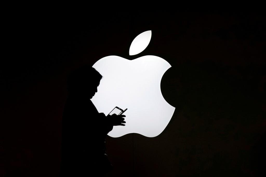 アップルのロゴの前でスマートフォンを操作する女性(ロイター)