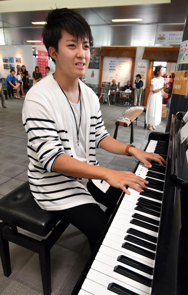 自らが設置を企画したストリートピアノに向かう青柳大空さん=8月31日、甲府市のJR甲府駅北口(渡辺浩撮影)