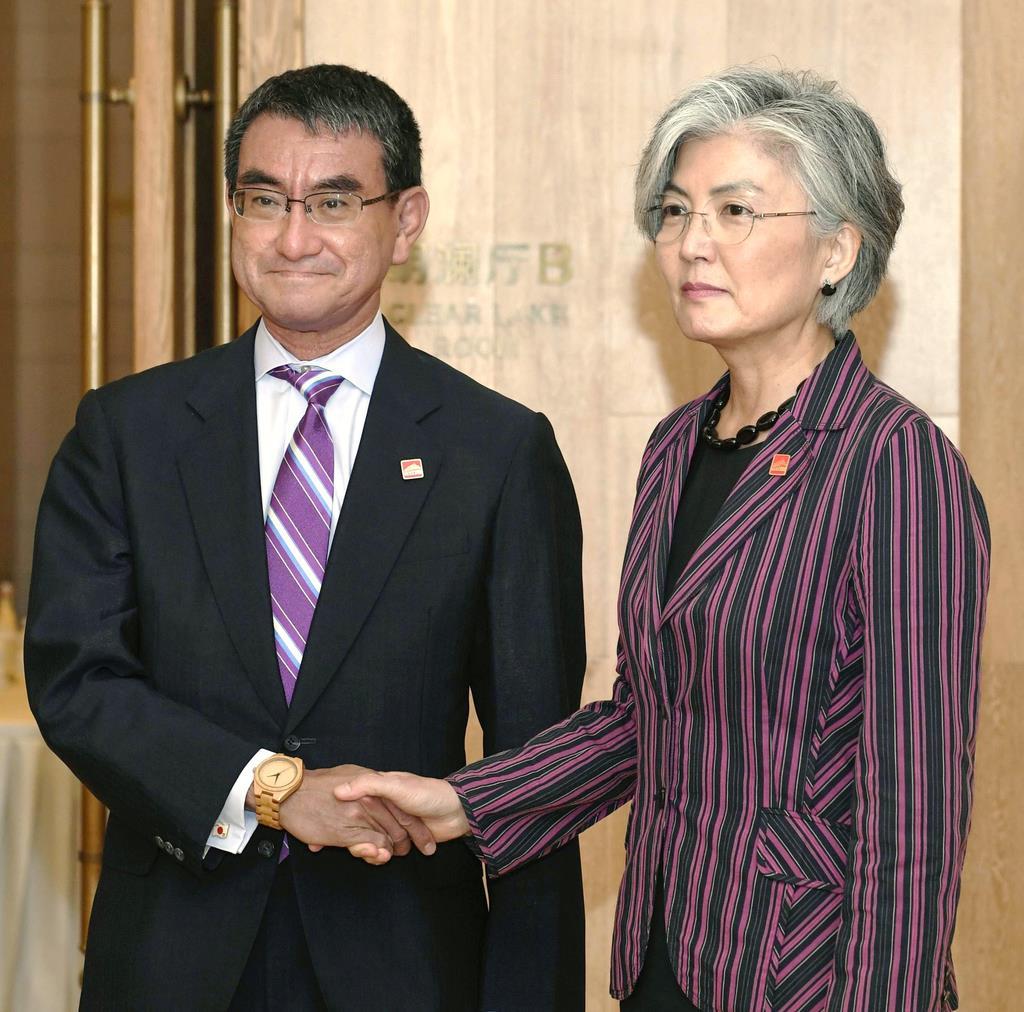 会談を前に握手する河野外相(左)と韓国の康京和外相=8月21日、北京郊外(共同)