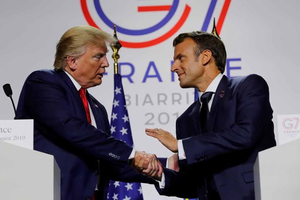 8月26日、仏ビアリッツでのG7サミット終了後、記者会見でトランプ米大統領(左)と握手するマクロン仏大統領(ロイター)