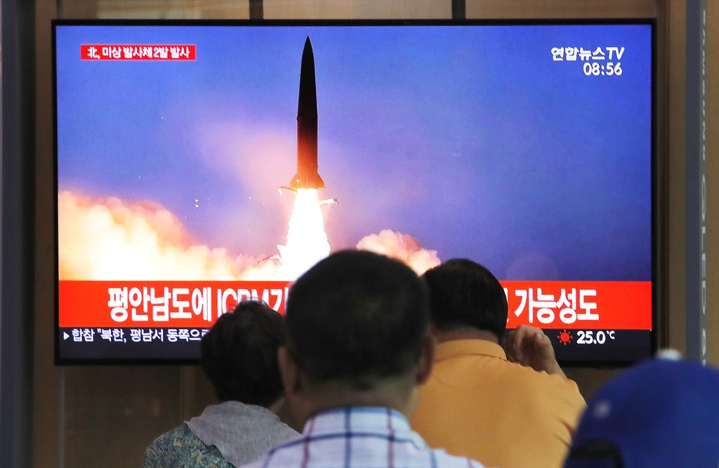 北朝鮮による飛翔体発射を報道するテレビを見る韓国の市民ら=10日、ソウル(AP)