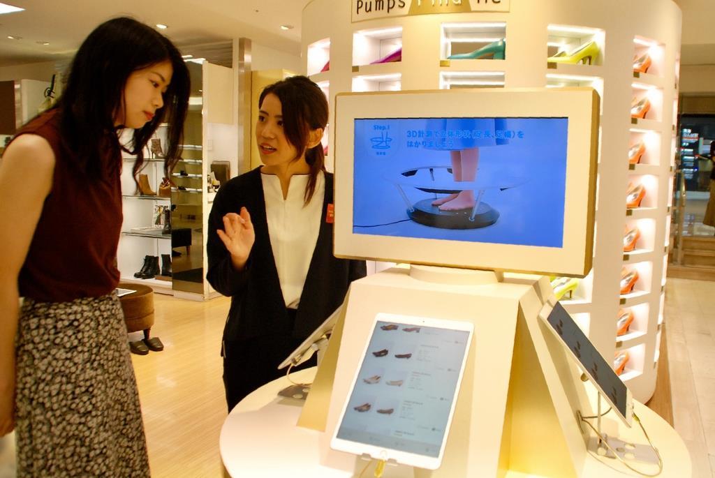 高島屋大阪店の新サービス「パンプス ファインド ミー」で足のサイズに合ったパンプスを探す女性客(左)=10日午後、大阪市中央区