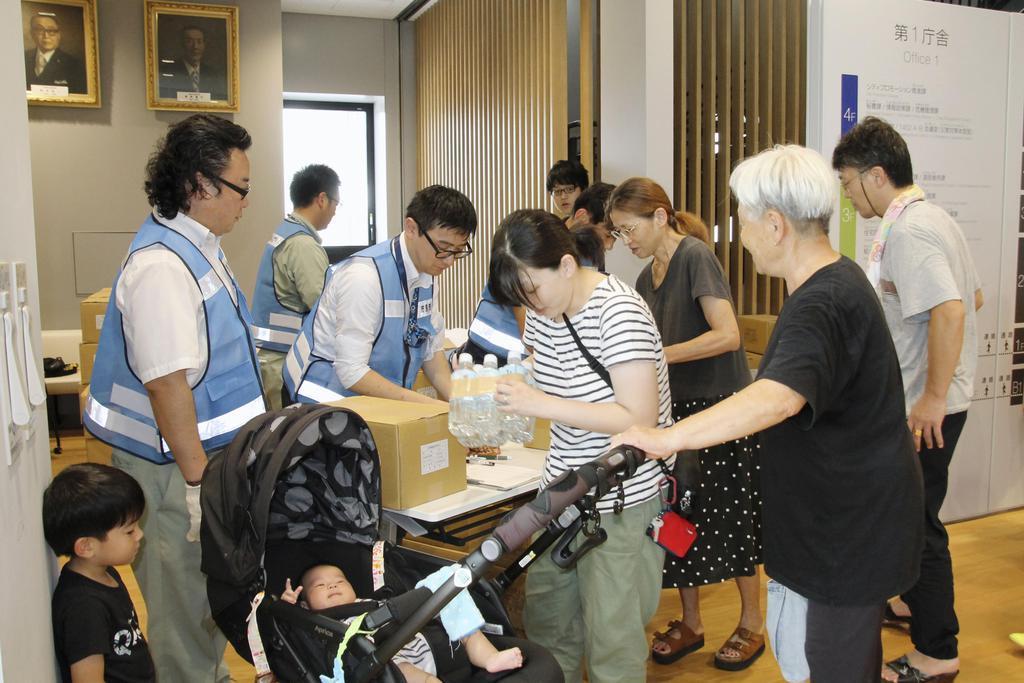 停電が続く千葉県市原市の市役所で飲料水を受け取る市民ら=11日午前