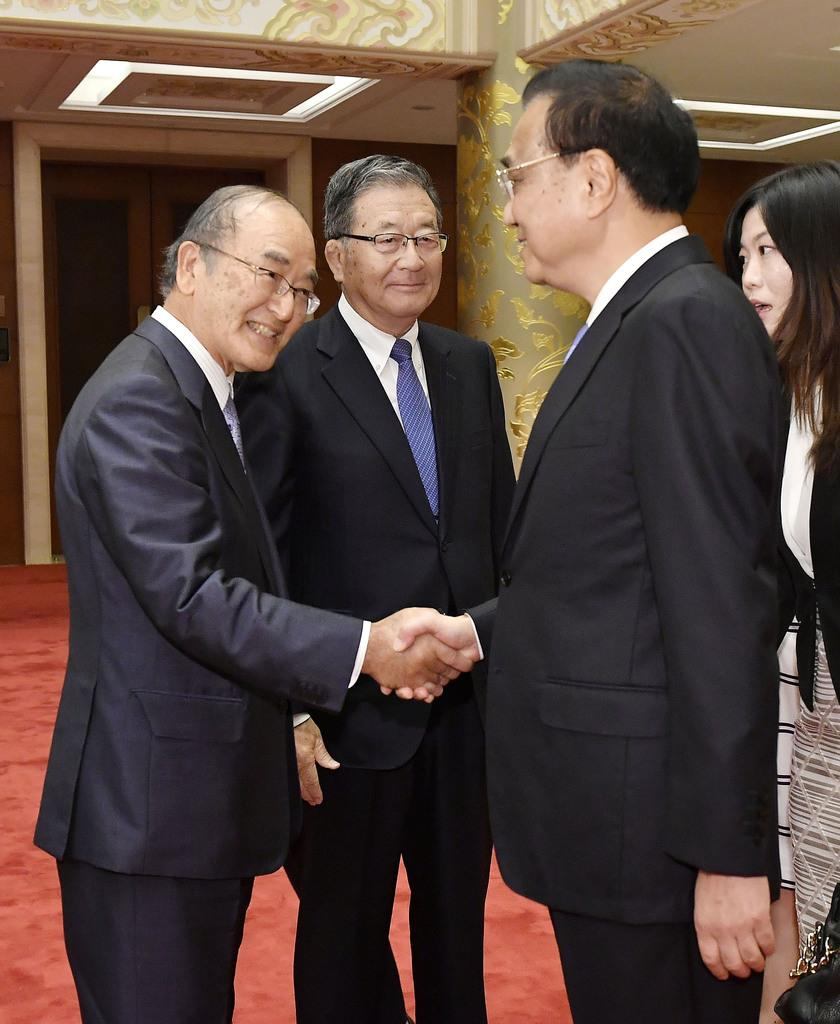 日本商工会議所の三村明夫会頭(左)と握手する中国の李克強首相。奥は日中経済協会の宗岡正二会長=11日、北京の釣魚台迎賓館(共同)