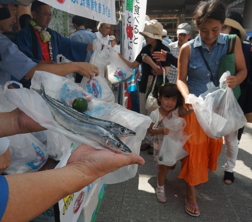 無料配布される塩サンマを求め、行基広場には長い列ができた=近鉄奈良駅前