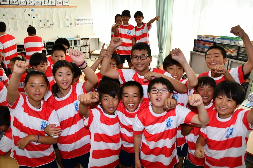 プレゼントされた特製ラガーTシャツを着て笑顔を見せる児童ら=大阪府東大阪市の英田北小学校
