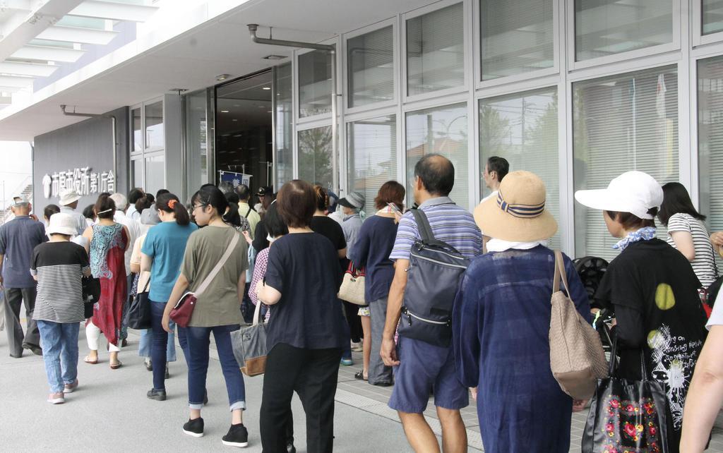 停電が続く千葉県市原市で、飲料水などを求め市役所に集まった市民ら=11日午前