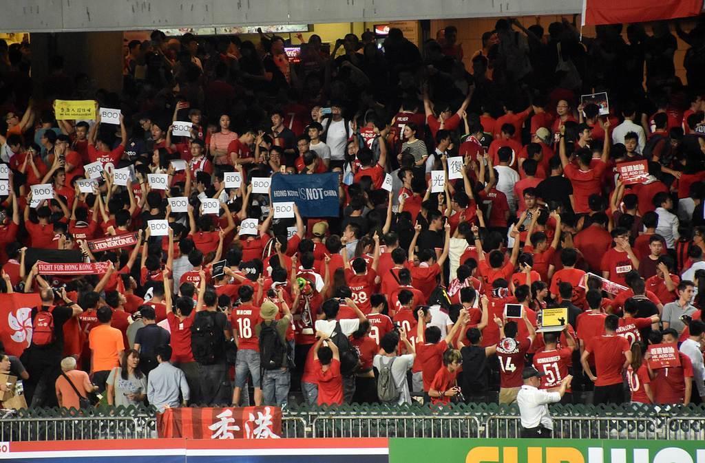 サッカーのワールドカップ(W杯)アジア2次予選のイラン戦で、中国国歌の演奏の際にピッチに背を向け、ブーイングを浴びせる香港サポーターら=10日夜、香港スタジアム(西見由章撮影)