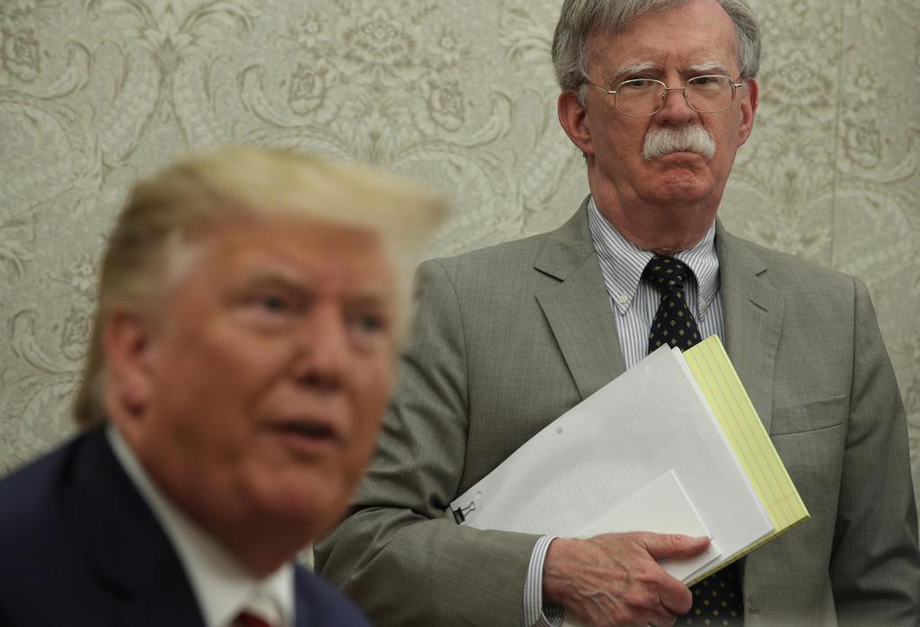 ホワイトハウスの執務室でトランプ米大統領(左)の話を聞くボルトン大統領補佐官=8月20日、ワシントン(ゲッティ=共同)