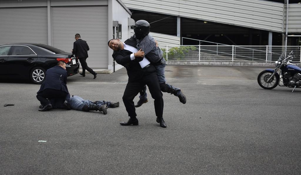 バイクから降りて攻撃してくる男を取り押さえる訓練を行う身辺警戒員=大津市