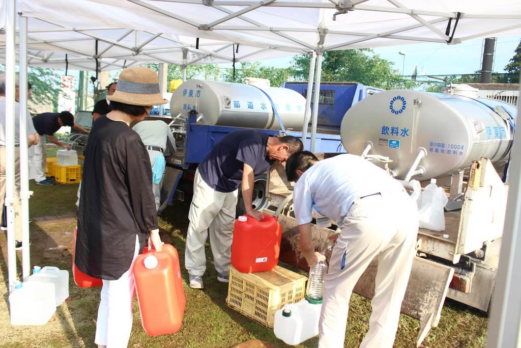 断水が続く中、住民らは多くのポリタンクを抱え給水所へ詰めかけていた=10日、伊東市八幡野の対島中学校(石原颯撮影)