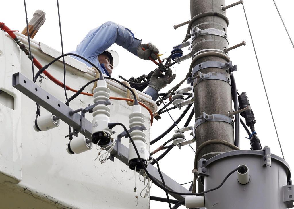 台風15号の影響による停電からの復旧作業を進める作業員=12日午後、千葉県富津市