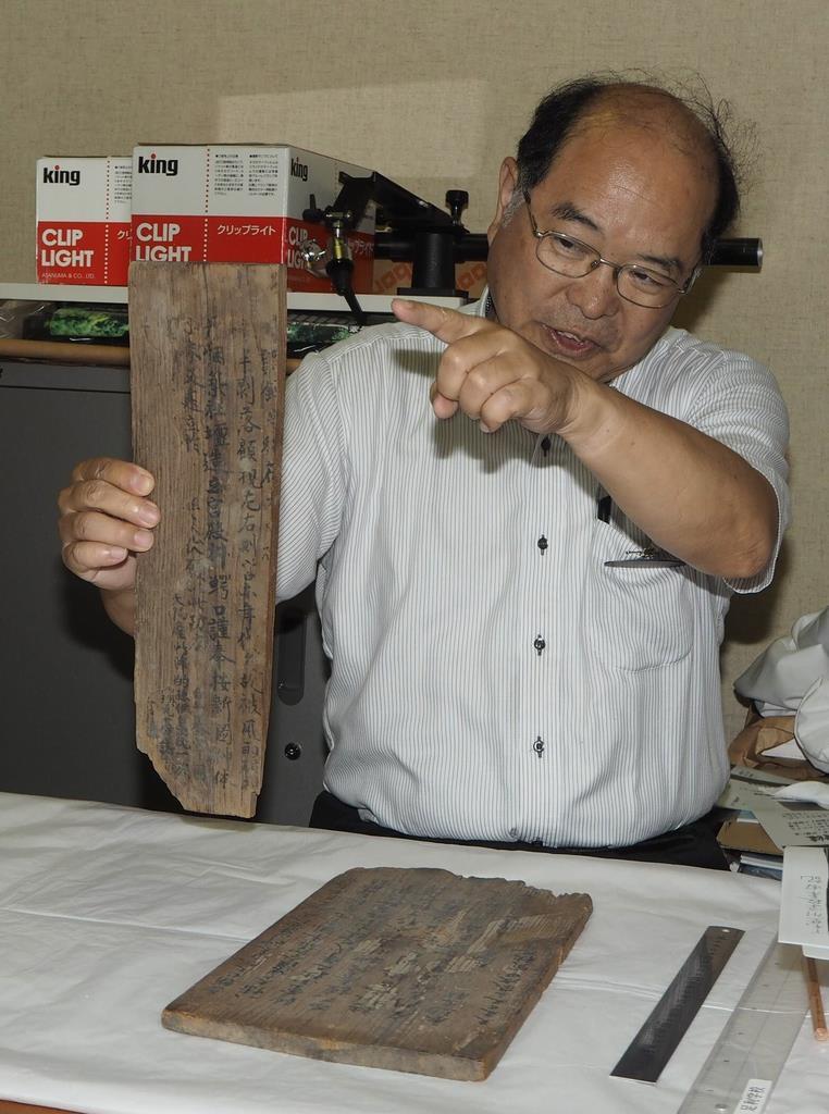 九華の記した木板を手に説明する史跡足利学校事務所の大沢伸啓所長=12日